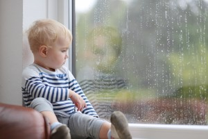 Cute baby girl looking outside through the window during rain